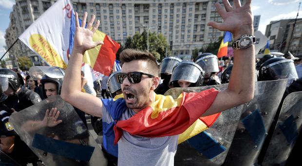 A protester shouts outside the government headquarters in Bucharest (AP Photo/Andreea Alexandru)