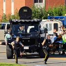 Police officers race to the area of the shooting in Fredericton, New Brunswick yesterday