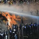 Riot police use a water canon (Vadim Ghirda/AP)