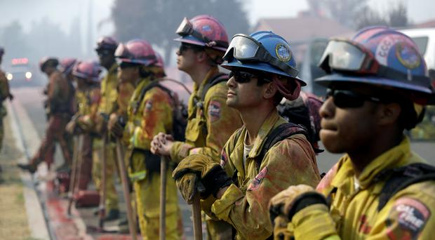 Fire crews line up as they watch a wildfire on a ridge top while protecting a residential area (Marcio Jose Sanchez/AP)