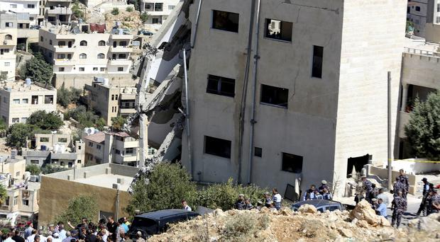 Jordanian security forces inspect the rubble after the side of a building collapsed (Raad Adayleh/AP)