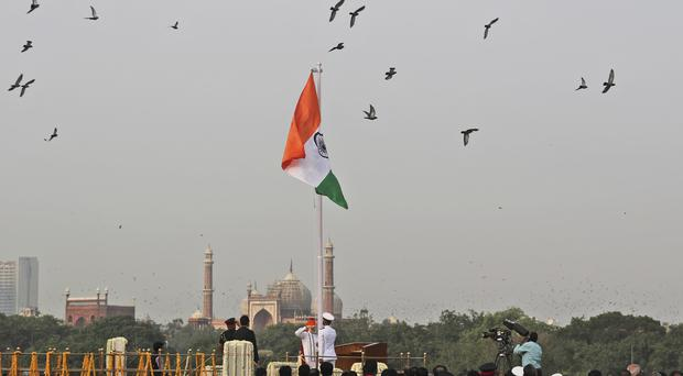 Indian PM Narendra Modi, centre , unfurls the national flag on the country's independence day (Manish Swarup/AP)