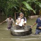 An elderly woman is rescued in a cooking utensil after her home was flooded in Thrissur, Kerala state( KK Najeeb/AP)