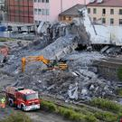 Firefighters remove debris of the collapsed Morandi highway bridge in Genoa (Luca Zennaro/ANSA/AP)