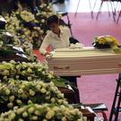 A woman wipes a small white coffin of a victim of the bridge collapse (Gregorio Borgia/AP)