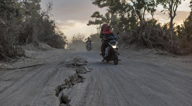 Motorists ride past a road torn apart by am earthquake earlier this month in Lombok (Fauzy Chaniago/AP)