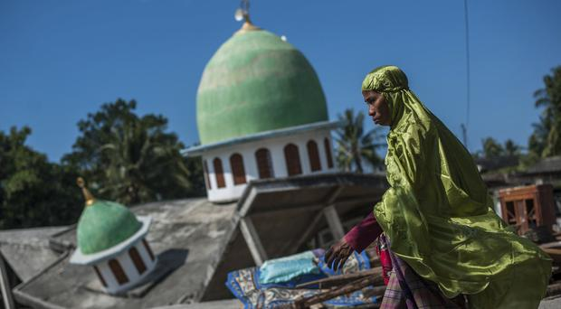 A Muslim woman walks past a collapsed mosque in Gangga, Lombok (Fauzy Chaniago/AP)