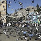 Men attend the Eid al-Adha prayers outside of Shah-e-Dushamshera mosque as pigeons fly in Kabul (Rahmat Gul/AP)