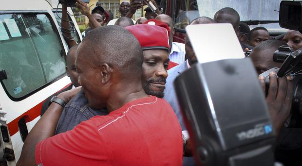 Bobi Wine is hugged by a supporter as he gets into an ambulance after leaving a courthouse (AP Photo)