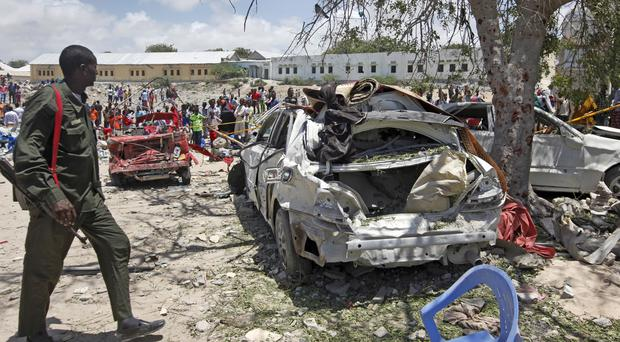 A Somali soldier walks near the wreckage of vehicles at the scene of the blast in Mogadishu (Farah Abdi Warsameh/AP)