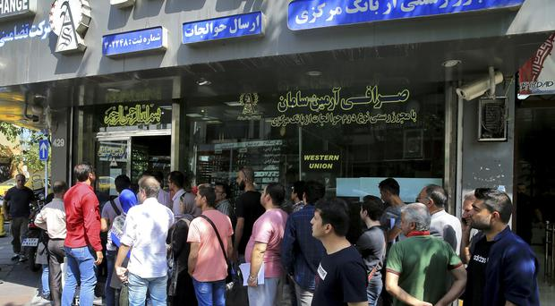 Queues outside a currency exchange shop in Tehran (AP)