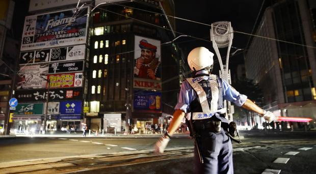 A police officer controls the traffic during a blackout following a strong earthquake in northern Japan (Hiroki Yamauchi/Kyodo News via AP)