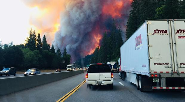 A fire rages as motorists travel on Interstate 5 in California (Jerri Tubbs/PA)