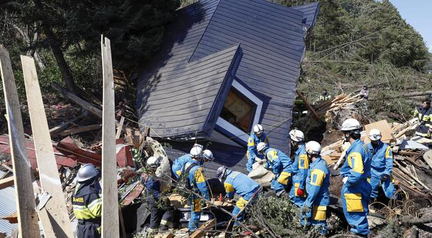 Police search for missing people around a house destroyed by a landslide (Masanori Takei/Kyodo News/AP)