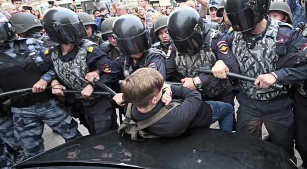 Russian police officers push a teenager during a rally protesting against retirement age hikes in St Petersburg (AP)