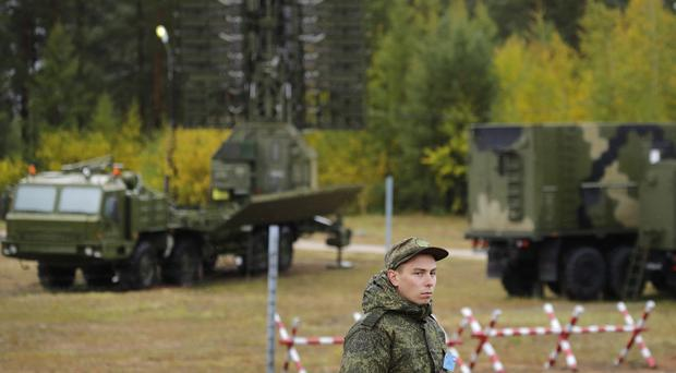 A Russian soldier stands in front of a radar deployed in a forest during the military exercises (Sergei Grits/AP)