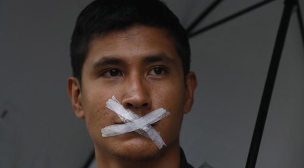 A student with his mouth taped shut participates in the march (Marco Ugarte/AP)