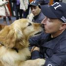 Sniffer dog Simon kisses his handler during the retirement ceremony (Fernando Vergara/AP)