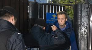 Police officers detain Russian opposition activist Alexei Navalny as he leaves a detention centre (Dmitry Serebryakov/AP)