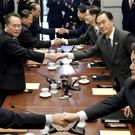 North Korean and South Korean representatives shake hands (Korea Pool/Yonhap via AP)