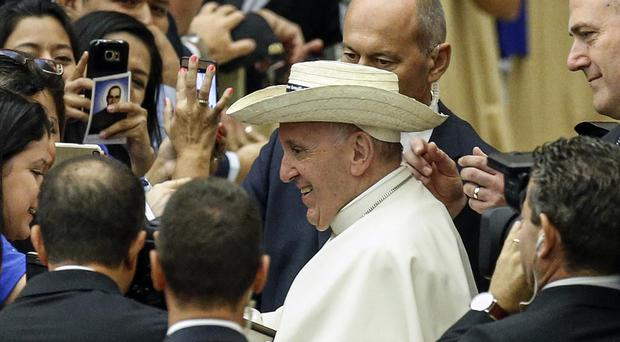 Pope Francis wears a hat given to him by a pilgrim (Fabio Frustaci/Ansa//AP)