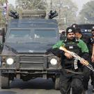 Pakistani police commandos escort a police van carrying Mohammad Imran (AP)