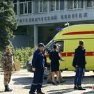 Policemen, medics and investigators stand near the college (Kerch Info News via AP)