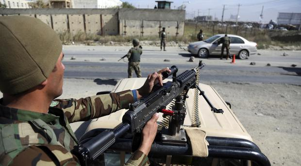 Afghan National army soldiers search a car at a checkpoint (AP)