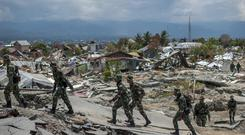 Indonesian soldiers walk at the earthquake-devastated neighbourhood of Balaroa in Palu (Fauzy Chaniago/AP)