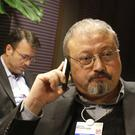File photo of Jamal Khashoggi speaking on his mobile phone at the World Economic Forum in Davos, Switzerland (Virginia Mayo/AP)