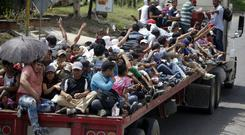 Honduran migrants who are travelling to the United States as a group, get a free ride in the back of a lorry in Guatemala (Moises Castillo/AP)