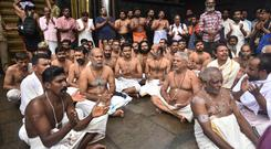 Hindu priests and temple staff sit in a protest against a ruling from India's top court (AP)
