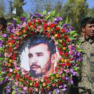 Military personnel held a photo of General Abdul Raziq, Kandahar police chief, who was killed by a guard, during his burial ceremony in Kandahar (STR/AP)