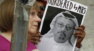 People hold signs during a protest at the Embassy of Saudi Arabia (Jacquelyn Martin/AP)