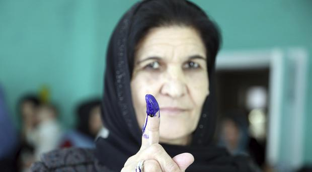 An Afghan woman shows her inked finger after casting her vote (Rahmat Gul/AP)