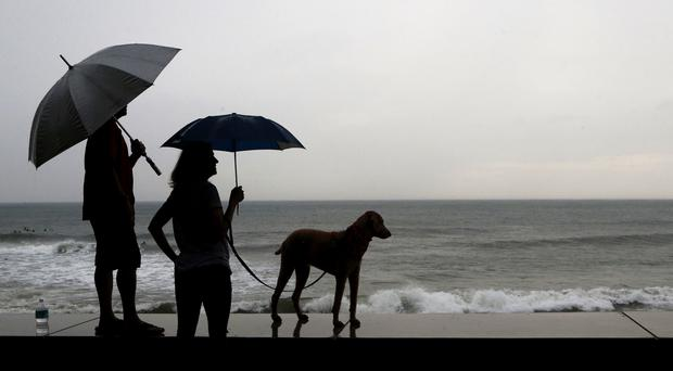 A couple and their dog stand of the seawall prior the landfall of Hurricane Willa, in Mazatlan, Mexico (AP Photo/Marco Ugarte)