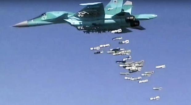 A Russian combat fighter bomber Su-34 unloads its bombs over a target in Syria (Russian Defense Ministry Press Service photo via AP, File)