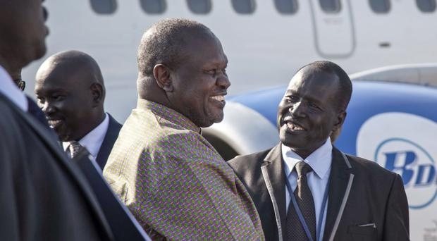 South Sudan's opposition leader Riek Machar, centre, is greeted as he arrives at the airport in Juba, South Sudan (AP Photo/Bullen Chol)
