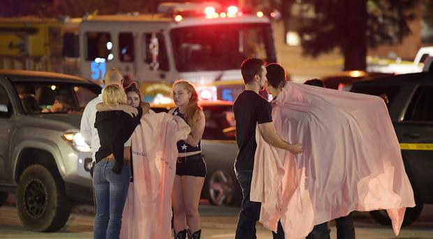 People comfort each other after the shooting (Mark J. Terrill/AP)
