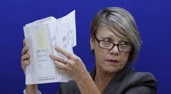 Betsy Benson, canvasing board chair holds ballots to be reviewed during a canvasing board meeting (Joe Skipper/AP)