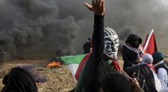 Protesters near the fence on Gaza Strip border with Israel on Friday (AP/Adel Hana)