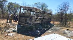 Emergency services stand near to a burnt out bus (AP)