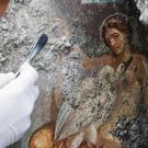 An archeologist cleans up the fresco Leda And The Swan (Cesare Abbate/Ansa/AP)