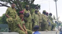 Security personnel on the back of a lorry wait to be paid at Rita Flynn Netball Centre in Port Moresby, Papua New Guinea (Jam Morales/AP)