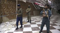 Afghan security personnel stand guard inside a wedding hall in Kabul, a day after a suicide attack (Rahmat Gul/AP)