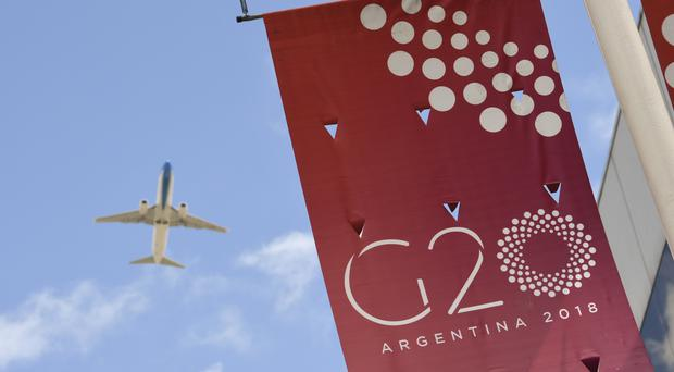 A plane flies over the G20 summit venue at the Costa Salguero Centre in Buenos Aires, Argentina (Gustavo Garello/AP)