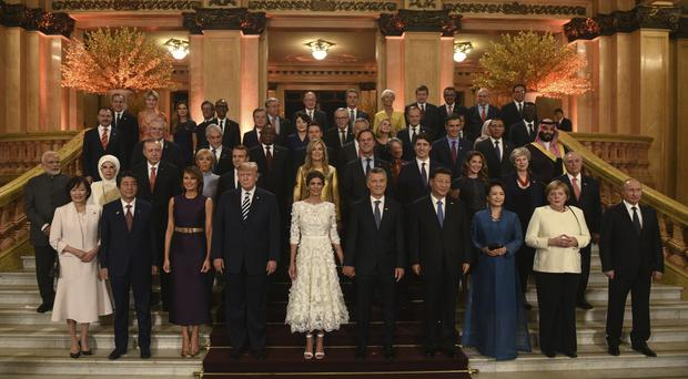 Leaders and their partners pose for a group photo prior to a gala dinner at the Colon Theatre in Buenos Aires (G20 Press Office via AP)