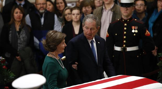 The former president put his hand on his father's flag-draped casket (AP/Patrick Semansky)