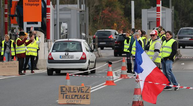 Demonstrators stand near toll gates on a motorway at Biarritz (AP Photo/Bob Edme)