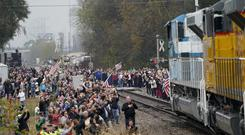 People pay their respects as the train carrying the casket of former President George HW Bush passes along the route from Spring to College Station, Texas (David J Phillip/AP)
